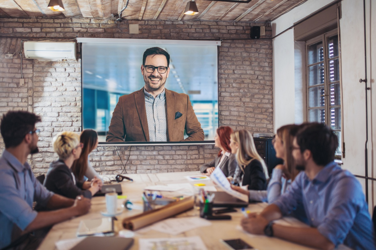 Business-people-looking-at-projector-during-video-conference-in-office-939098810_2125x1416-1